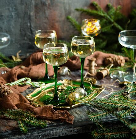 vintage wine glasses with champagne on old wooden green tray stands on rustic table christmas toys, fir tree branches. new year still life Foto de archivo - 133846046