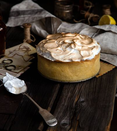 homemade tasty baked lemon tart with shortbread crust and whipped meringue on top stands on rustic wooden table Foto de archivo - 133846047