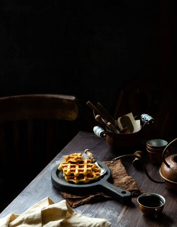 homemade baked waffles with maple syrup or honey on wooden boards stands on rustic table with copper teapot, cups, napkin Foto de archivo - 133846048