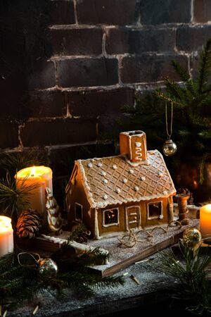 homemade gingerbread house decorated with icing stands on rustic table with candles, fir tree branches Foto de archivo - 133846050