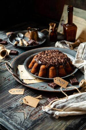homemade chocolate cake with melted chocolate and chocolate flakes on top on metal vintage plates Foto de archivo - 133846052