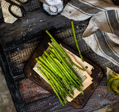 overhead shot with fresh green asparagus on wooden board stands on rustic wooden table with eggs, salt, grey napkin Foto de archivo - 133846053