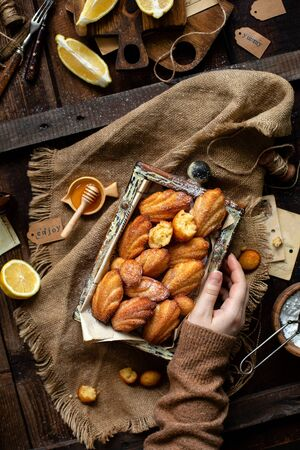overhead shot of homemade tasty french shell shaped biscuit dessert madeleine in wooden box on rustic table with sackcloth, honey, lemon Foto de archivo - 133846056