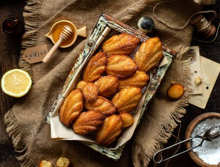 overhead shot of homemade tasty french shell shaped biscuit dessert madeleine in wooden box on rustic table with sackcloth, honey, lemon Foto de archivo - 133846055