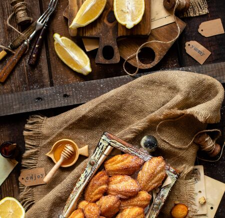 overhead shot of homemade tasty french shell shaped biscuit dessert madeleine in wooden box on rustic table with sackcloth, honey, lemon Foto de archivo - 133846057