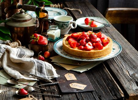 Homemade delicious strawberry tart or pie with sweet glazed berries on top stands on vintage plate with green ornament on rustic wooden table with bottles, plates, spoons, old letters, coconut flakes Foto de archivo - 133846058