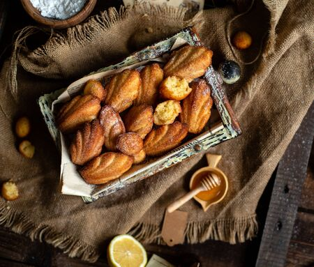 overhead shot of homemade tasty french shell shaped biscuit dessert madeleine in wooden box on rustic table with sackcloth, honey, lemon Foto de archivo - 133846061