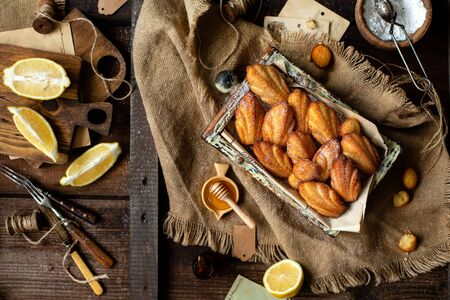 overhead shot of homemade tasty french shell shaped biscuit dessert madeleine in wooden box on rustic table with sackcloth, honey, lemon Foto de archivo - 133846062