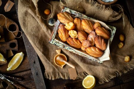 overhead shot of homemade tasty french shell shaped biscuit dessert madeleine in wooden box on rustic table with sackcloth, honey, lemon Foto de archivo - 133846067