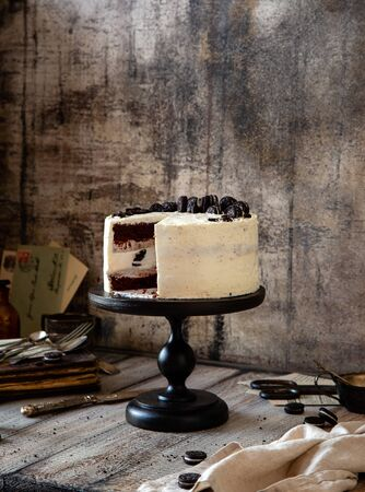 Homemade tasty cut round cake with white cream, chocolate biscuit layers, black cookies on black wooden cake stand on grey table, selective focus Foto de archivo - 133846071