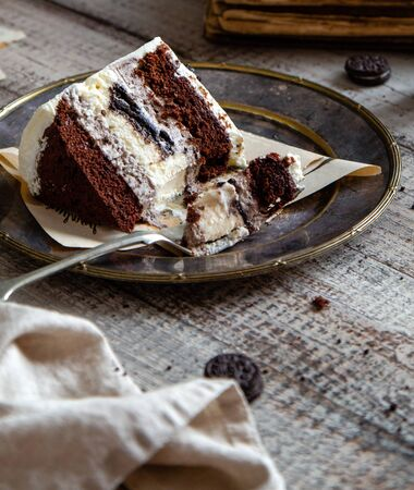 Homemade tasty slice of chocolate biscuit cake with white cream, black cookies on vintage metal plate on grey table, selective focus Foto de archivo - 133955398