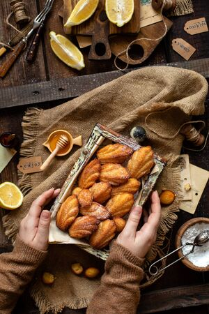 overhead shot of homemade tasty french shell shaped biscuit dessert madeleine in wooden box on rustic table with sackcloth, honey, lemon Foto de archivo - 133955400