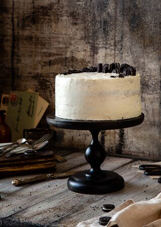 Homemade tasty whole round cake with white cream, black cookies on black wooden cake stand on grey table, selective focus Foto de archivo - 133955401