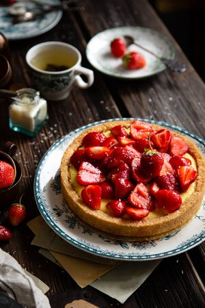 Homemade delicious strawberry tart or pie with sweet glazed berries on top stands on vintage plate with green ornament on rustic wooden table with bottles, plates, spoons, old letters, coconut flakes Foto de archivo - 133955406