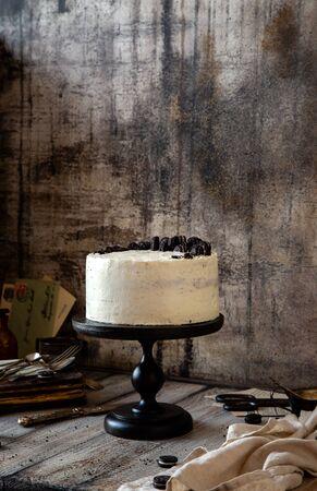 Homemade tasty whole round cake with white cream, black cookies on black wooden cake stand on grey table, selective focus Foto de archivo - 133955404