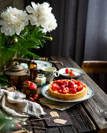 Homemade delicious strawberry tart or pie with sweet glazed berries on top stands on vintage plate with green ornament on rustic wooden table with bouquet of peonies Foto de archivo - 133955407
