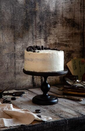 Homemade tasty whole round cake with white cream, black cookies on black wooden cake stand on grey table, selective focus Foto de archivo - 134323985