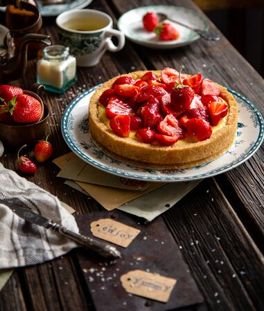 Homemade delicious strawberry tart or pie with sweet glazed berries on top stands on vintage plate with green ornament on rustic wooden table with bottles, plates, spoons, old letters, coconut flakes Foto de archivo - 134324010