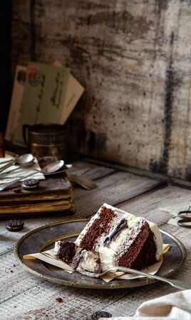 Homemade tasty slice of chocolate biscuit cake with white cream, black cookies on vintage metal plate on grey table, selective focus Foto de archivo - 134324017