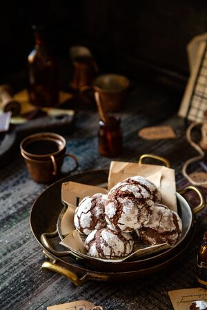 homemade chocolate christmas crinkle cookies in copper plates on dark wooden table, selective focus Foto de archivo - 134324012