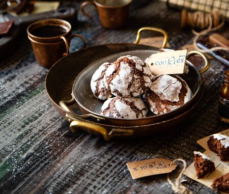 homemade chocolate christmas crinkle cookies in copper plates on dark wooden table, selective focus Foto de archivo - 134324011