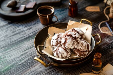 homemade chocolate christmas crinkle cookies in copper plates on dark wooden table, selective focus Foto de archivo - 134644395