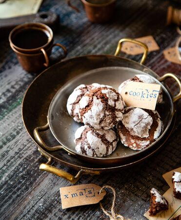 homemade chocolate christmas crinkle cookies in copper plates on dark wooden table, selective focus Foto de archivo - 134644396