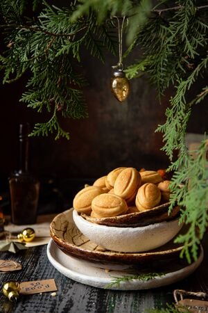 traditional russian Christmas walnut shell cookies in ceramic bowls on wooden table with fir tree branches Foto de archivo - 134644397