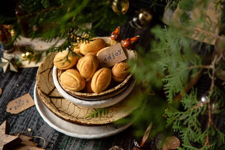traditional russian Christmas walnut shell cookies in ceramic bowls on wooden table with fir tree branches Foto de archivo - 134644398