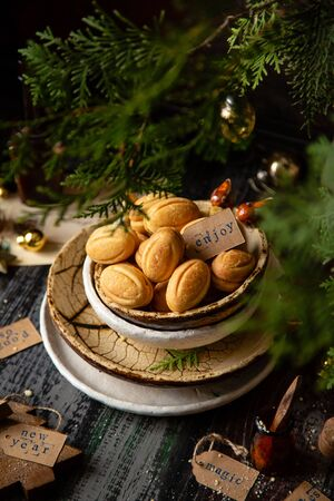 traditional russian Christmas walnut shell cookies in ceramic bowls on wooden table with fir tree branches Foto de archivo - 134644401