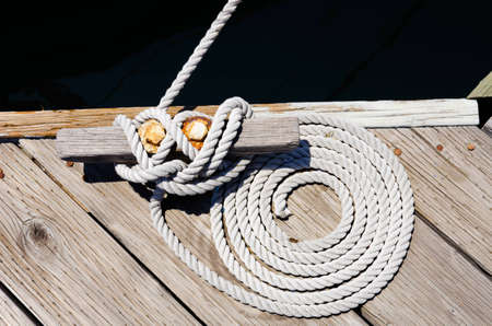This is a photograph of a coiled rope tying a boat to a dock.