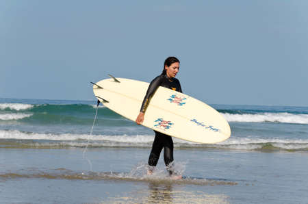Newport Beach, California, USA - May 25, 2011: A female surfer is seen in the morning on the beach enjoying the beautiful weather. This is a popular location for surfers.