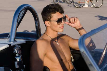 Knappe jonge man in cabrio sportwagen Stockfoto