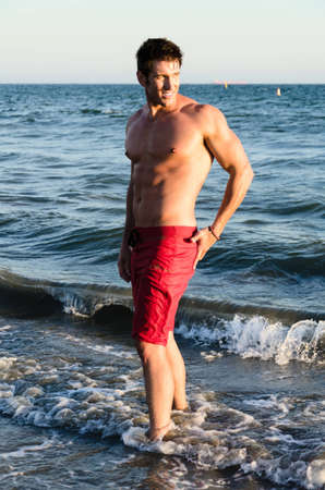 Gorgeous male model standing in the surf at the beach  photo