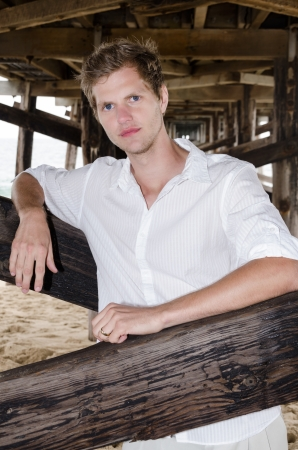 Good looking young man at the beach under the pier  photo