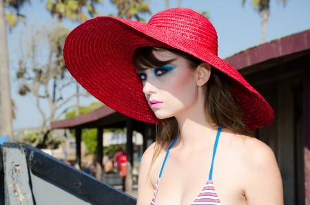 make up eyes: Stunning young lady with red hat posing in beautiful Newport Beach California