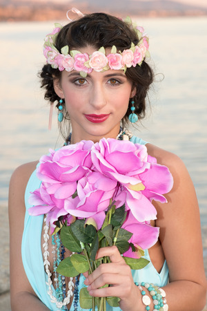 Beautiful young lady at the beach holding a bouquet of flowers. Doheny State Beach, California, USA