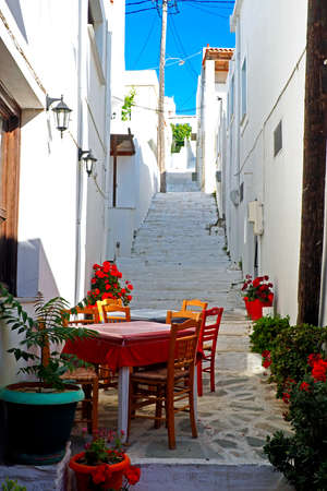 One of the charms of Mykonos, the Greek island of Cyclades, are the small terraces with their colorful tables and chairs on the ground floor of the white houses of the narrow cobbled streets