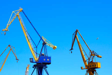 beautiful yellow naval cranes, standing out against the azure blue sky of the port of Piraeus, near Athens in Greece Stock Photo