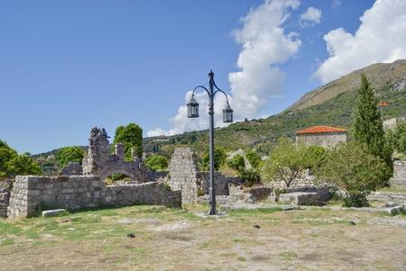Lone streetlight among ancient ruins.