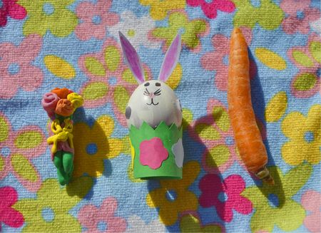eastertime: Children handmade: Easter bunny made of an egg shell with plasticine flowers and carrot on the flower background. Stock Photo