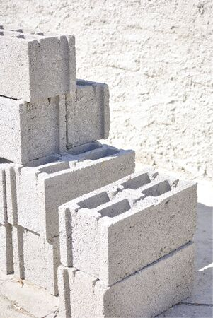 Group of concrete blocks used in construction. With concrete wall on the background.