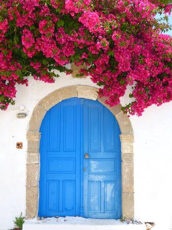 Typically blue Greek door with pink bougainvillea flowers, Greece