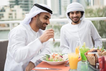 hombre arabe: Dos �rabes Emiratis hombres est�n disfrutando de comida en un restaurante