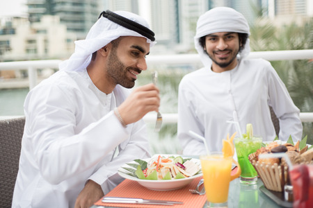 speaking: Two Arab Emirati Men Are Enjoying Food in a Restaurant