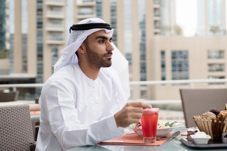 kandura: Arab Emirati Man Sitting in a Restaurant and Looking Forward
