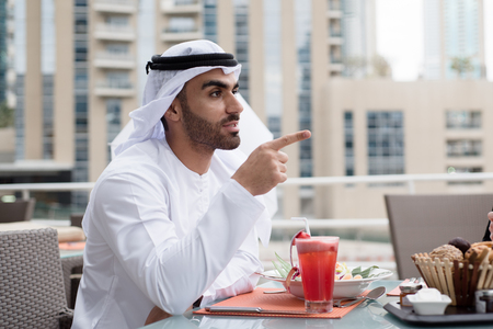 looking forward: Arab Emirati Man in a Restaurant Looking forward and Pointing Finger