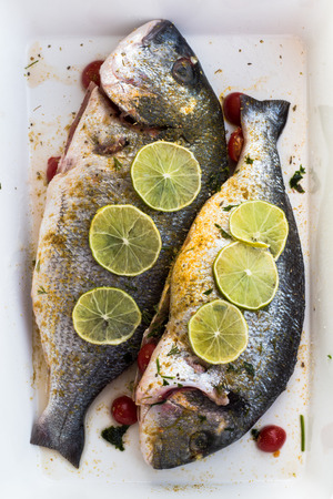 dorade: Two raw Sea Bream fish stuffed with greens, cherry tomatoes and decorated with lime ready to go to oven.