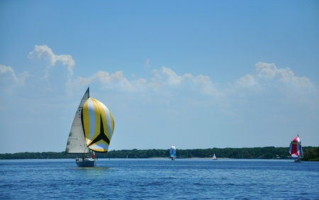 spinnaker: Zaporozhye City, Ukraine - June 13, 2010 -  A yacht with a yellow spinnaker during a regatta on the river Dnieper