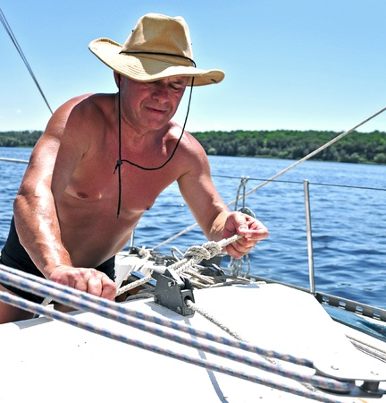 Zaporozhye City, Ukraine - June 13, 2010 - A yachtsman tying a knot on his yacht during a regatta on the river Dnieper